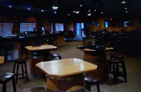 Inside of a restaurant with wooden tables and black bar stools