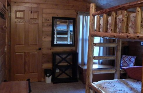 Bedroom with carpet, wood paneling on the walls, and wooden bunk bed