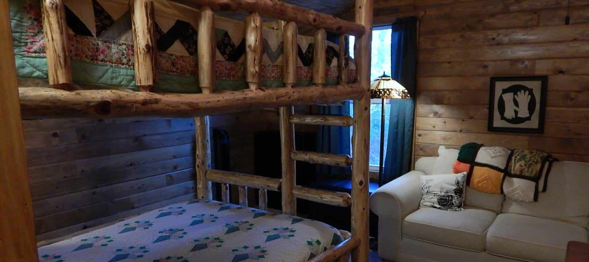 Bedroom with carpet, wood paneling on the walls, wooden bunk bed, and love seat
