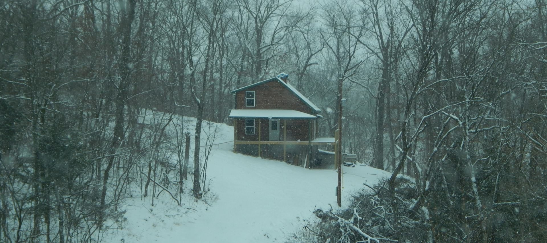 Brown cabin in the woods surrounded by trees and snow