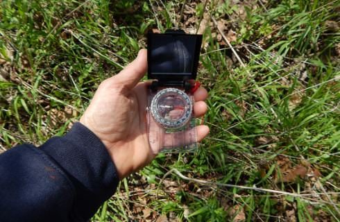 Close up view of man holding a compass with green grass in background