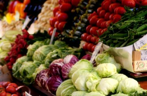 Stacked fresh green, purple, red, and yellow vegetables