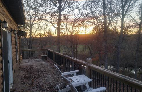 Exterior view of the cabin standing on the deck looking out to the river, trees and setting sun